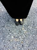 Close Up on Woman`s Feet Wearing Black Sandals & Dress, Standing Commemorate on Stone Royalty Free Stock Images
