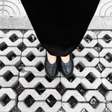 Close Up on Woman`s Feet Wearing Black Sandals & Dress, Standing Commemorate on the Street. Great For Any Use Royalty Free Stock Photography
