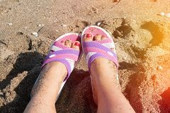 Foot in shales on sand beach Royalty Free Stock Photos