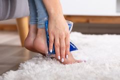 Woman Applying Ice Gel Pack On Her Ankle. Close-up Of A Woman`s Hand Applying Ice Gel Pack On Her Ankle stock photos