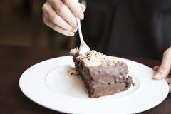 Close-up of woman's hand cutting chocolate pastry Stock Images