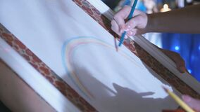 Close-up of woman`s hand drawing rainbow on easel. Close-up of woman`s hand drawing rainbow on the album white paper on the easel at the party stock video