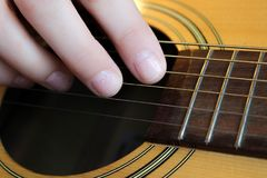Woman`s hand playing a guitar. Close up of woman`s hand with glittery nail polish playing a guitar Stock Photo