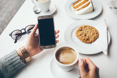 Close-up of woman`s hand holding cell phone while drinking coffee and eating oat cookie. Stock Images