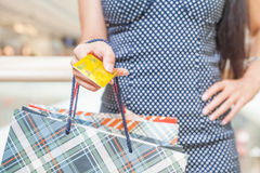 Close-up of woman's hand holding credit card and bags Royalty Free Stock Photography
