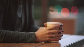 Close-up of woman s hand holding a cup of coffee, fume from the tea cup. Blurred lights, urban street stock footage