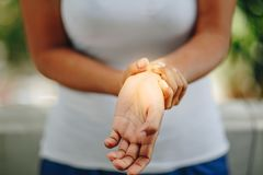 Close up woman`s hand holding her wrist stock images