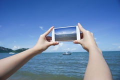 Close up of woman's hand holding smart phone, mobile, smart phone over blurred beautiful blue sea and fishing boat Stock Photo