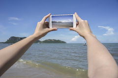 Close up of woman's hand holding smart phone, mobile, smart phone over blurred beautiful blue sea and fishing boat Stock Image