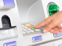 Close-up of woman`s hand inserting debit card into an ATM machin. E stock photography