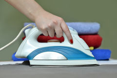 Close-up of woman's hand ironing clothes on the table against th Stock Images
