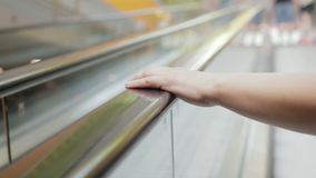 Woman climbs up the escalator from underground Parking to the store. Close - up of a woman`s hand lies on the railing of the escalator stock video footage