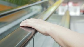 Woman climbs up the escalator from underground Parking to the store. Close - up of a woman`s hand lies on the railing of the escalator stock footage