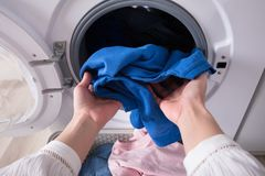 Woman`s Hand Putting Blue Cloth Into Washing Machine royalty free stock images