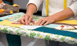 Close up of woman`s hand sewing patchwork. Close up of woman`s hand sewing a patchwork Royalty Free Stock Images
