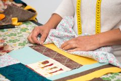 Close up of woman`s hand sewing patchwork. A close up of woman`s hand sewing patchwork Stock Image