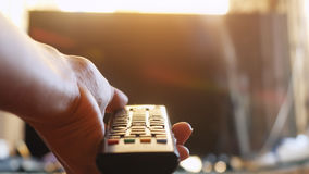 Close up of woman`s hand with a television remote control at sunset time Stock Photography