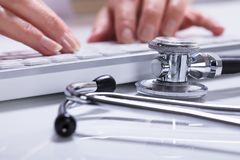 Woman`s Hand Typing. Close-up Of Woman`s Hand Typing With Stethoscope On Desk stock image