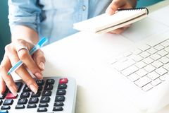 Close up woman`s hand using calculator, Work space desk with lap Royalty Free Stock Images