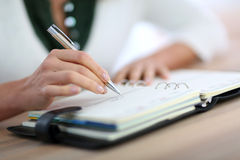 Close-up of woman's hand writing in agenda Stock Photography