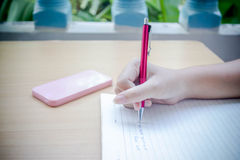 Close up of woman's hand writing. On notebook Royalty Free Stock Photo