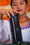 Close-up woman& x27; s handen die sapmaker gebruiken, die plastic deel neerdrukken die wortel opnemen in machine, gezonde levenss Stock Afbeeldingen