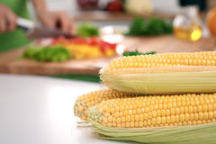 Close up of  woman`s hands cooking in the kitchen. Corn on the cob Royalty Free Stock Photography