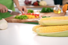 Close up of  woman`s hands cooking in the kitchen. Corn on the cob Royalty Free Stock Images