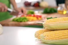 Close up of  woman`s hands cooking in the kitchen. Corn on the cob Stock Photo