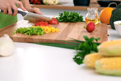 Close up of woman`s hands cooking in the kitchen. Housewife slicing fresh salad. Royalty Free Stock Images