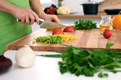 Close up of woman`s hands cooking in the kitchen. Housewife slicing fresh salad. Royalty Free Stock Photo
