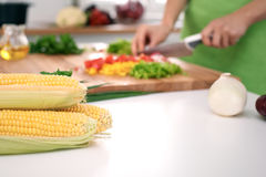Close up of woman`s hands cooking in the kitchen. Housewife slicing fresh salad. Royalty Free Stock Image
