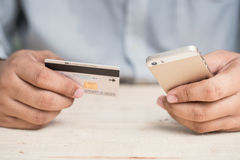 Close-up woman`s hands holding a credit card and using cell phon Stock Image