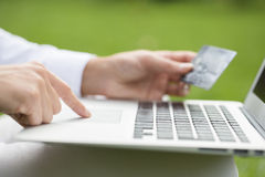 Close-up woman's hands holding a credit card and using computer Royalty Free Stock Image