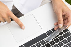 Close-up woman's hands holding a credit card and using computer Royalty Free Stock Photos
