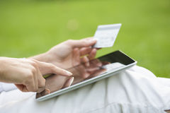 Close-up woman's hands holding a credit card and using tablet pc Royalty Free Stock Images