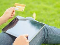 Close-up woman`s hands holding a credit card and using tablet pc for online shopping stock photography