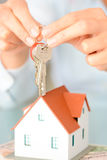 Close-up of woman`s hands holding a model house and a key suggesting house acquisition or rental. Close-up of woman`s hands holding a small model house and a key Stock Photo