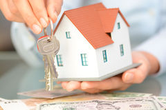 Close-up of woman`s hands holding a model house and a key suggesting house acquisition or rental. Close-up of woman`s hands holding a small model house and a key Royalty Free Stock Image