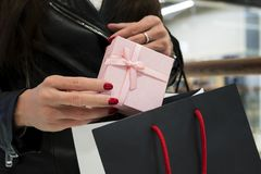 Close up of woman's hands holding packed up small present and shopping bag. Lady putting a pink box into the package at mall stock image