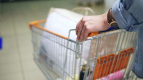 Close up of a woman`s hands holding and pushing a trolley with goods in the supermarket. Backside view.  stock footage