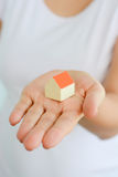 Close-up of woman`s hands holding a small model house. Close-up of woman`s hands holding a small toy house Stock Photography