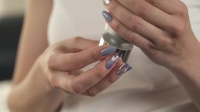 A close up of woman's hands holding a tube with cream. She untwists the lid, squeezes out some cream on her finger. A close up of woman s hands holding a stock footage