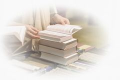 Close-up of woman`s hands with pile of books, bookstore. Education, school, study, reading fiction concept. Light. Close-up of woman`s hands with a lot of Stock Image