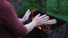 Close up woman's hands near the fire stock video footage