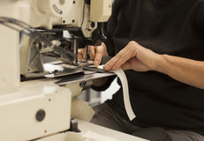 Close up of woman's hands operating a sewing machine. Stock Image