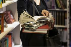 Close-up of woman`s hands with pile of books, bookstore. Education, school, study, reading fiction concept. Close-up of woman`s hands with several books Royalty Free Stock Photo