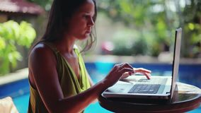 Brunette woman typing on a laptop computer by the swimming, exotic summer vacation. 1920x1080. hd stock footage
