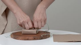 A close-up of woman`s hands wrapping a bar of soap. She is winding a rope around the parcel and makes a secure bow.