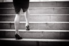 Close up of woman`s legs and leather shoes while walking up to t. He stairs in the city in black and white tone Stock Images